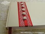 bijela knjiga gostiju s crvenom trakom i bijelim ružama