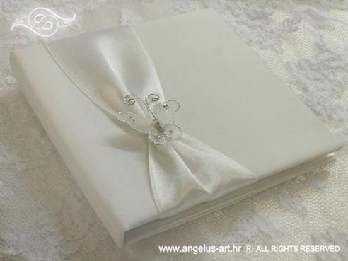 bijela knjiga kao jastučić za prstenje s bijelim leptirom