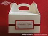 bijela kutija za kolače s crvenom trakom i imenima mladenaca