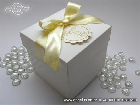 bijela kutija za kolače s krem mašnom i ukrasnim kartončićem