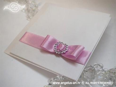 bijela pozivnica s rozom masnom i brosem u obliku srca