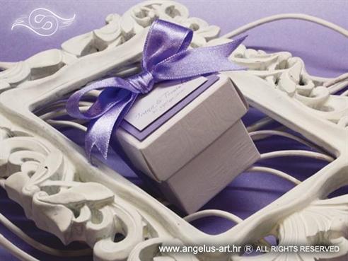 konfetna kutijica za vjenčanje s konfetnim bombonima ukrašena ljubičastom mašnom